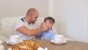 Junger Vater, der sein kleines Sohngesicht nach dem Mittagessen säubert Stockfotos