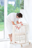 Junger Vater, der sein neugeborenes Baby in Krippe setzt Stockfotografie