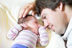 Junger Vater, der seine neugeborene Tochter umarmt Stockbilder