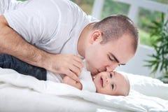 Junger Vater, der seinem Baby einen Kuss gibt Stockfotografie