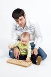 Junger Vater, der seinen kleinen Sohn unterrichtet, Musik zu spielen stockbild
