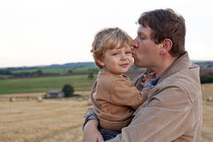Junger Vater, der Sohnkuß auf goldenem Strohfeld gibt Stockfoto