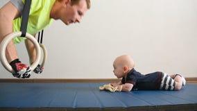 Junger Vater gedrängt auf die gymnastischen Ringe Nahe bei ihm spielt Lüge ein kleines Baby mit einem Spielzeug Mann küsst das Ki stock footage