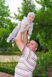 Junger Vater, der seinen Sohn in seinen Armen hält Stockfotografie