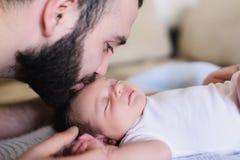 Junger Vater küsst sein neugeborenes Baby lizenzfreies stockfoto