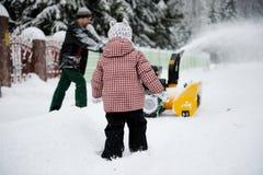 Junger Vater lässt Schneegebläse laufen Lizenzfreie Stockbilder