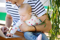 Junger Vater mit seinem Baby, das an Laptop arbeitet oder studiert Stockbilder