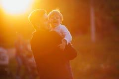 Junger Vater mit seinem kleinen Jungen gegen Sonnenschein Stockbilder