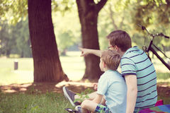 Junger Vater mit weniger Sonne am Sommerpark Lizenzfreie Stockfotografie