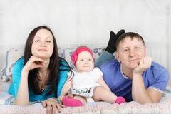 Junger Vater, schöne Mutter und Baby liegen auf Bett Stockfoto