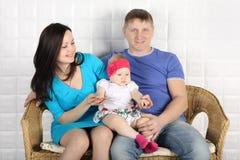 Junger Vater, schöne Mutter und Baby sitzen auf Sofa Lizenzfreie Stockbilder