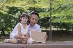 Junger Vater seine Tochter zu Rettungsgeld in Sparschwein für bessere Zukunft unterrichten lizenzfreie stockfotos