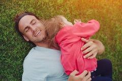 Junger Vater umarmt sein Energiebaby, das versucht zu entgehen, glückliche Familie im Park stockfotos