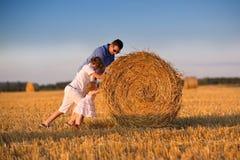 Junger Vater und childrem zwei, die auf dem Gebiet bei Sonnenuntergang spielt Lizenzfreie Stockfotos