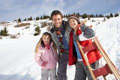 Junger Vater und Kinder im Schnee mit Schlitten stockbild