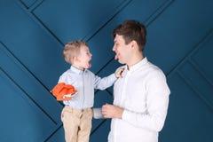 Junger Vater und kleiner Sohn setzten heraus Zungen für einander lizenzfreie stockfotografie