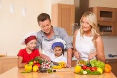 Junger Vater und Mutter, die zusammen Salat zubereitet Stockfotografie