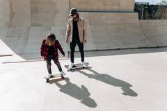 Junger Vater und seine Sohnfahrskateboards in einem Rochenpark mit den Dias ?u?er am sonnigen Tag lizenzfreie stockfotos