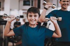 Junger Vater und Sohn, die Übungen im Sport-Verein tut stockbilder