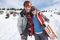Junger Vater und Sohn im Schnee mit Schlitten stockfotografie