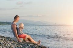 Junger Vater und Sohn sitzen auf dem Strand gegen den Hintergrund des Meeres und der Stadt im Abstand Lizenzfreie Stockbilder