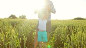 Junger Vater- und Sohnweg auf dem Gebiet und Spaß haben stock video