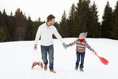 Junger Vater und Tochter, die in Schnee mit Sle geht Stockbild