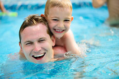 Junger Vater und wenig Sohnschwimmen im Pool Lizenzfreies Stockbild