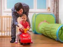 Junger Vater unterrichtet sein Kind, Spielzeugauto zu fahren Vati spielt mit Tochter stockfoto