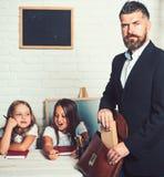 Junger Vater, welche zu Hause seinen T?chtern mit Schulprojekt hilft Mann setzte Buch in Tasche ein stockfotos