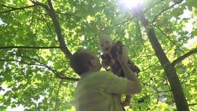 Junger Vateraufzug seine glückliche Babytochter unter Tulpenbaum im Park 4K stock video