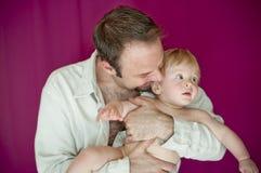 Junger Vati, der blondes Baby anhält Stockbilder