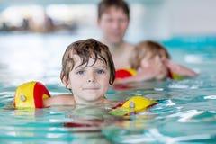 Junger Vati, der seine zwei kleinen Söhne unterrichtet zu schwimmen Lizenzfreie Stockfotos