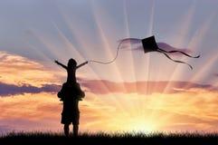 Junger Vati mit dem Kind, das mit Drachensonnenuntergang spielt Stockbild