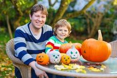 Junger Vati und sein kleiner Sohn, die Steckfassung-Olaterne für Halloween herstellt Stockfoto