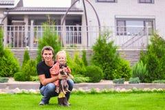 Junger Vati und seine kleine Tochter mit ihrem Welpen auf Hintergrund ihr Haus stockbilder