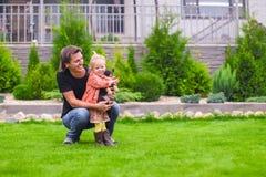 Junger Vati und seine kleine Tochter mit ihrem Welpen auf Hintergrund ihr Haus lizenzfreies stockbild