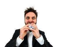 Junger verärgerter Geschäftsmann beim Essen des balled Papiers Lizenzfreie Stockfotos