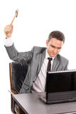 Junger verärgerter Geschäftsmann mit einem Hammer, der einen Laptop zertrümmert Lizenzfreies Stockbild