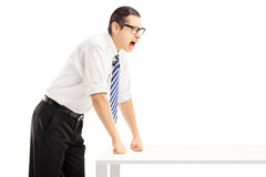 Junger verärgerter Mann auf einem Tabellenschreien Stockbild