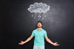 Junger verärgerter Mann, der über Tafel mit gezogenem raincloud schreit Stockbilder