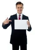 Junger Verkäufer, der in Richtung zur unbelegten Anschlagtafel zeigt stockfoto