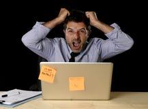 Junger verrückter betonter Geschäftsmann, der das hoffnungslose Arbeiten im Druck mit Laptop-Computer schreit Stockfotos