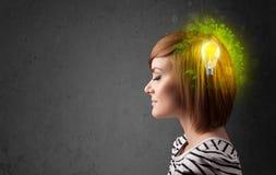 Junger Verstand, der an grüne eco Energie mit Glühlampe denkt Stockbild