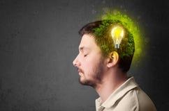 Junger Verstand, der an grüne eco Energie mit Glühlampe denkt Stockfotografie