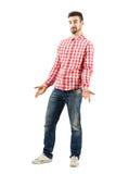 Junger verwirrter ungewisser Mann beim Zucken des karierten Hemds Stockfotos