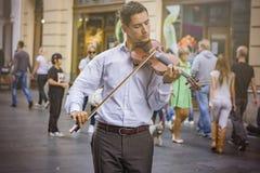 Junger Violinist, der auf einer Straße spielt Stockbild