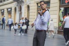 Junger Violinist, der auf einer Straße spielt Stockfotografie