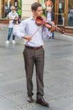 Junger Violinist, der auf einer Straße spielt Lizenzfreie Stockbilder