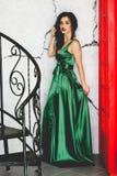 Junger vorbildlicher Brunette in der grünen Kleideraufstellung Stockbild